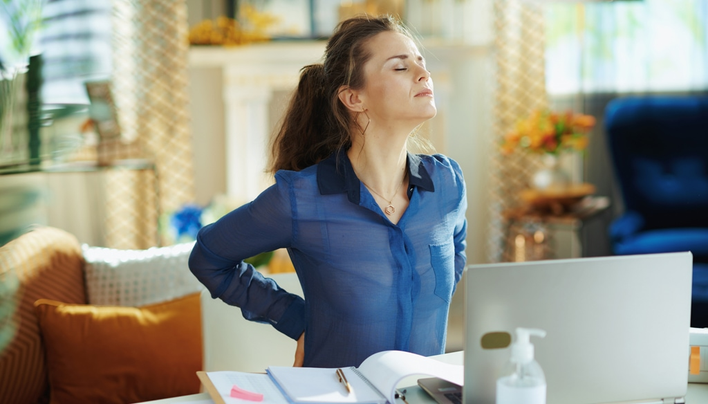 Woman with back pain. CBD pain cream.