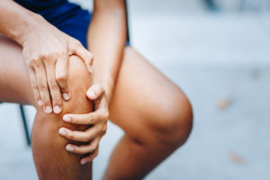 Woman holding painful knee. CBD cream for pain.